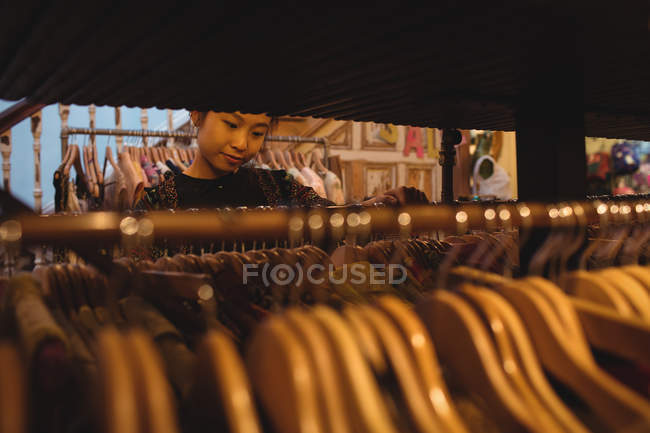 Young woman selecting clothes on hangers at apparel store — Stock Photo