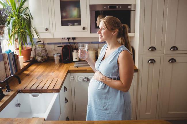 Беременная женщина пьет воду на кухне дома — стоковое фото