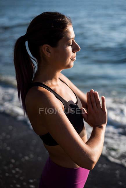 Высокий угол зрения Красивая женщина медитирует на пляже в солнечный день — стоковое фото