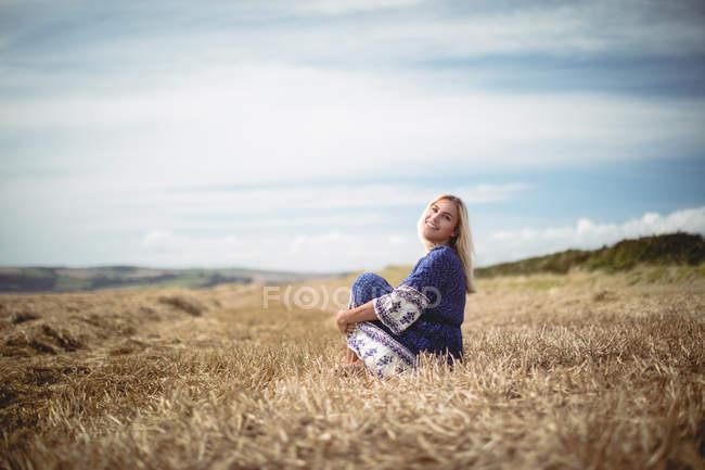 Усміхаючись привабливий блондинка жінка, що сидить у сфері — стокове фото