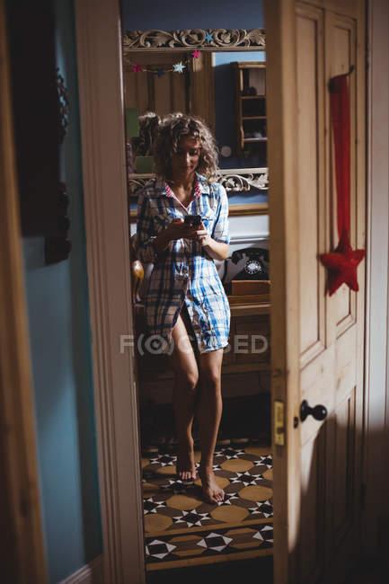 Hermosa mujer usando el teléfono móvil en casa - foto de stock