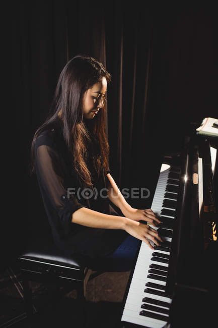 Красивая женщина, играет на фортепиано в музыкальной студии — стоковое фото