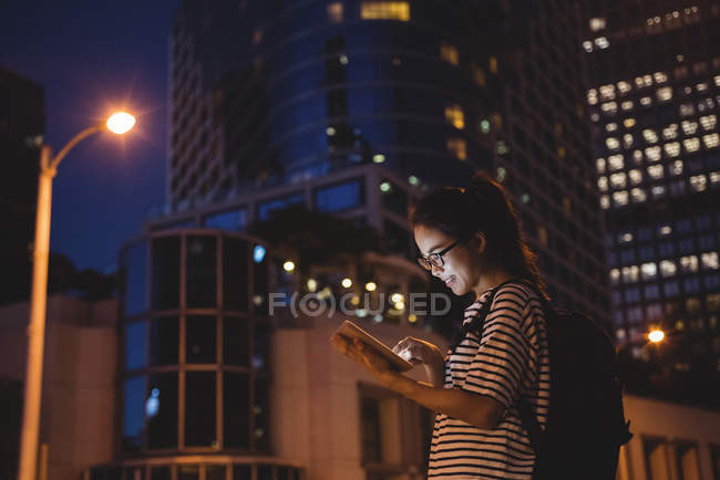 Young woman using digital tablet on street at night — Stock Photo