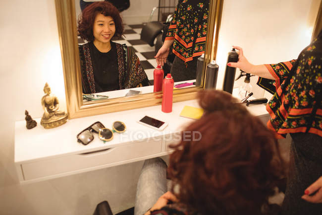 Femme souriante assise devant le miroir de salon de coiffure — Photo de stock
