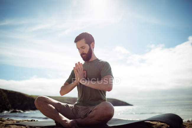 Man performing yoga on beach — Stock Photo