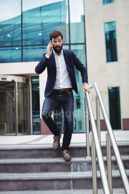 Businessman talking on mobile phone while walking on stairs — Stock Photo