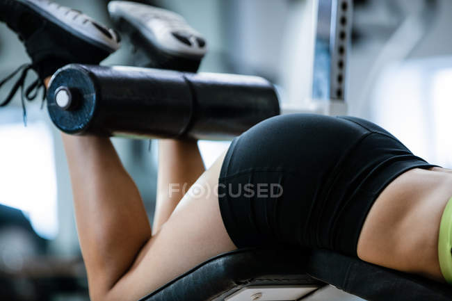 Woman performing exercise on bench press in gym — Stock Photo