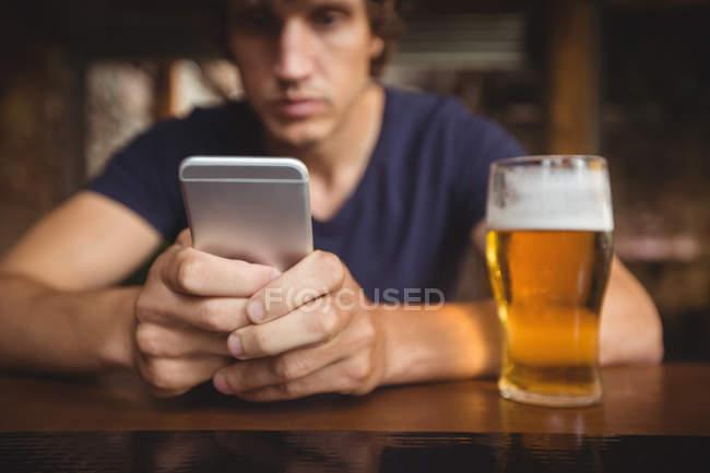 Людина за допомогою мобільного телефону з пивом склом на столі в м. бар — стокове фото
