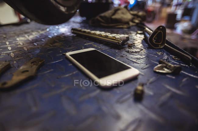 Мобільний телефон на workbench в промислових механічних майстерень — стокове фото