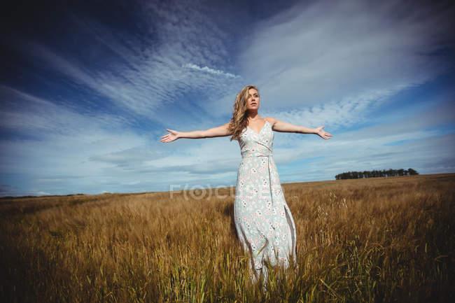 Mulher de pé com os braços estendidos no campo de trigo no dia ensolarado — Fotografia de Stock