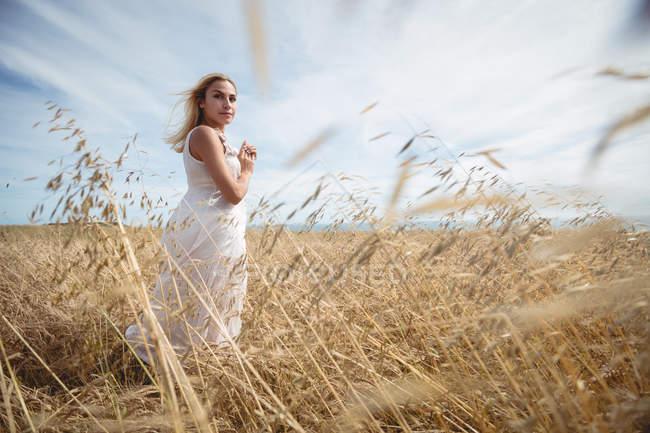 Selektiver Fokus der blonden Frau, die auf dem Feld steht und in die Kamera schaut — Stockfoto