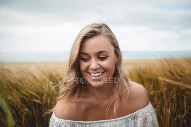 Smiling woman standing in wheat field on sunny day — Stock Photo