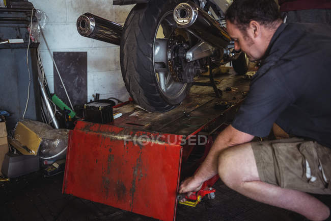 Mechanic using hydraulic lift in workshop — Stock Photo