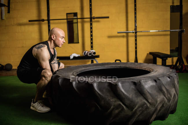 Side view of handsome athletic sportsman lifting heavy tire in gym — Stock Photo
