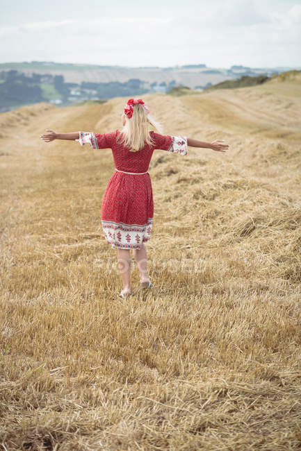 Rear view of carefree blonde woman standing in field with open arms — Stock Photo