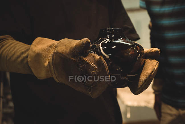Glassblower holding glass bowl at glassblowing factory — Stock Photo