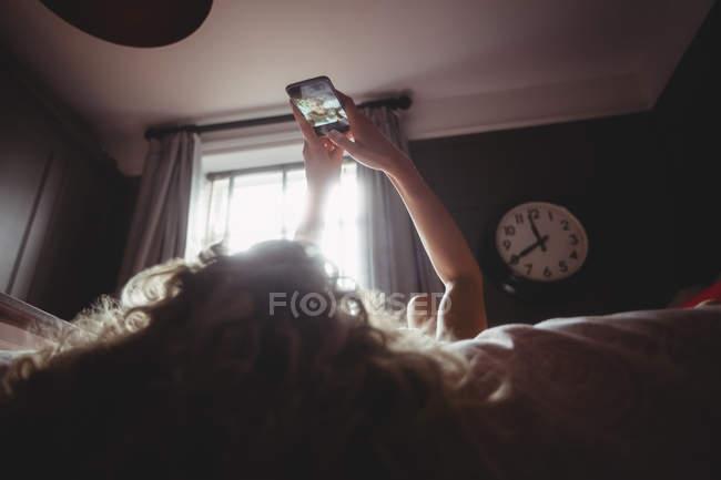 Жінка, негативно selfie на мобільний телефон у спальні будинку — стокове фото