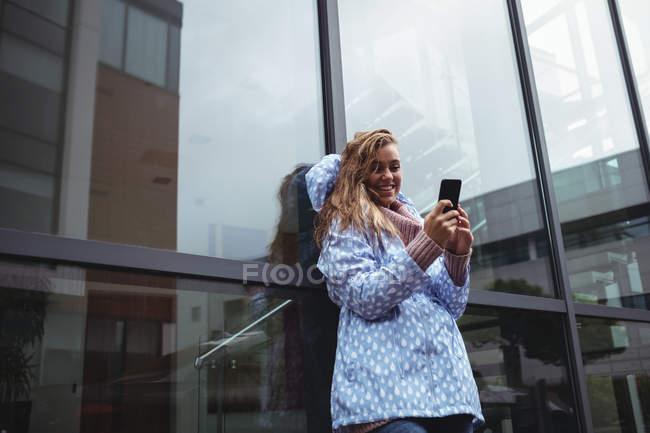 Красивая улыбающаяся женщина в обманщице и со смартфоном — стоковое фото