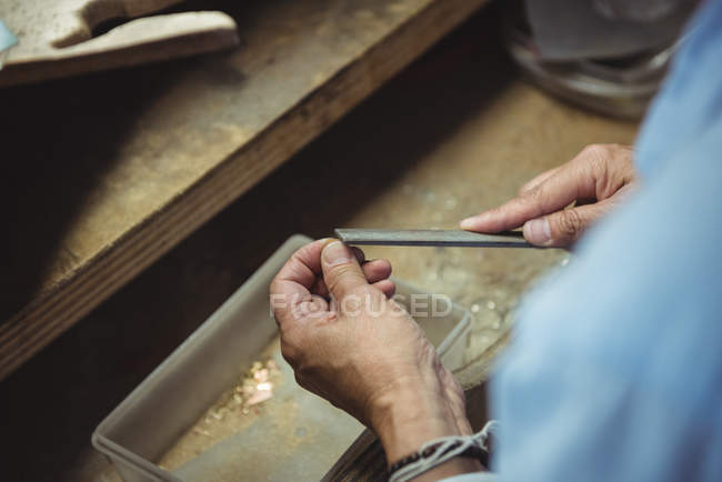 Hands of craftswoman using tool in workshop — Stock Photo