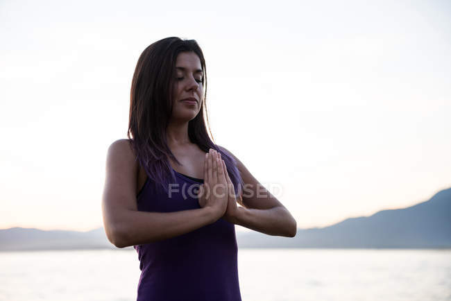 Красивая женщина медитирует на пляже в солнечный день — стоковое фото