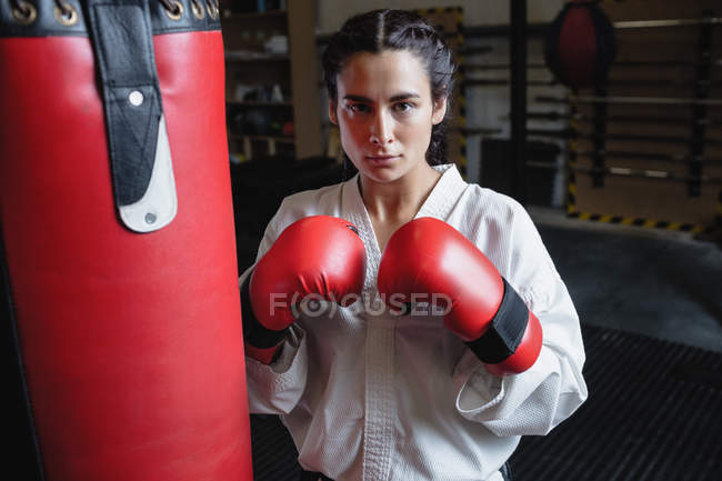 Portrait of woman in karate kimono and boxing gloves standing near punching bag in fitness studio — Stock Photo