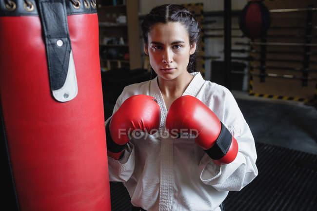 Ritratto di donna in kimono karate e guanti da boxe in piedi vicino al sacco da boxe in palestra — Foto stock