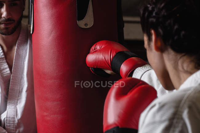 Cropped image of Man and woman practicing karate with punching bag in studio — Stock Photo
