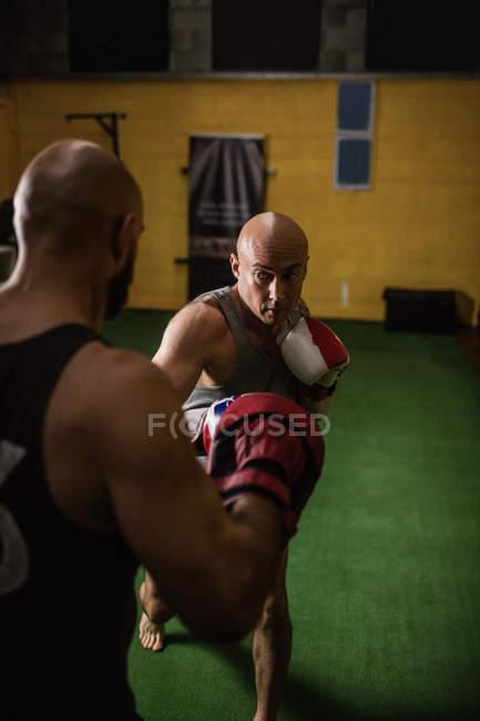 Foyer sélectif de deux boxeurs thai pratiquant la boxe dans la salle de gym — Photo de stock