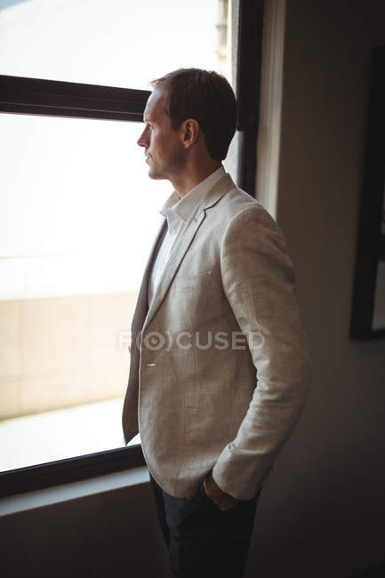 Thoughtful businessman looking through window at office — Stock Photo