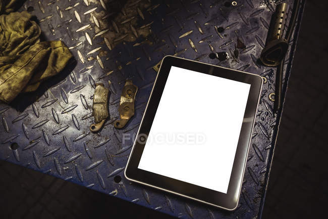 Digital tablet on workbench at industrial mechanical workshop — Stock Photo