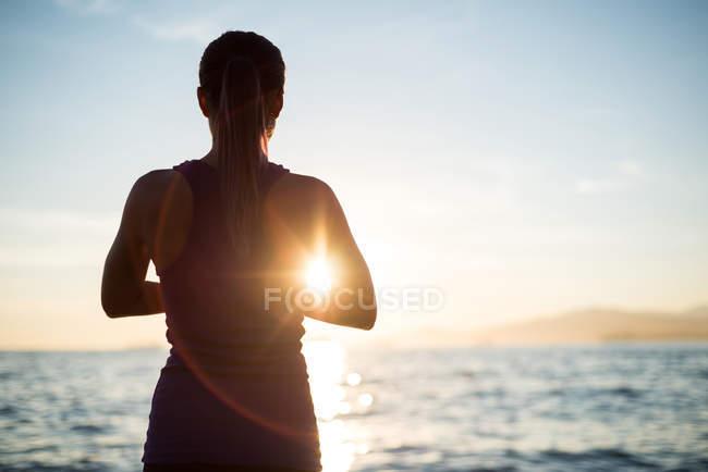 Вид сзади женщины, занимающейся йогой на пляже во время заката — стоковое фото