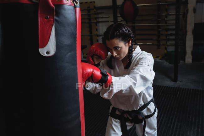 Frauen üben Karate mit Boxsack im Fitnessstudio — Stockfoto