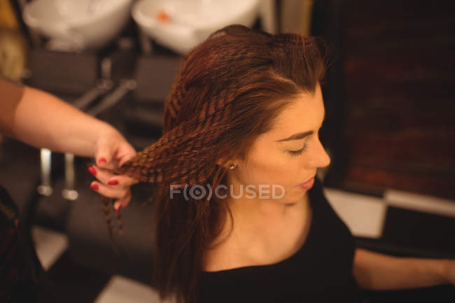 Belle femme coiffer ses cheveux au saloon — Photo de stock