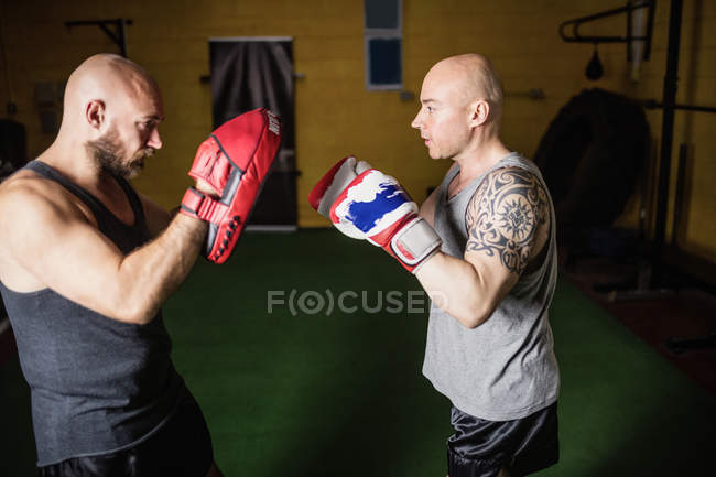 Side view of two athletic thai boxers practicing in gym — Stock Photo