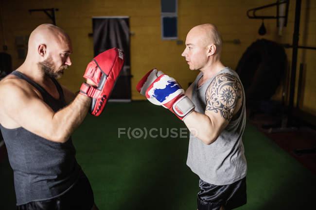 Seitenansicht von zwei athletischen thailändischen Boxern, die im Fitnessstudio üben — Stockfoto