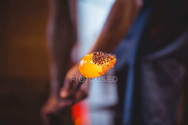Close-up of colored glass attaching to a piece of hot molten glass by glassblower at glassblowing factory — Stock Photo