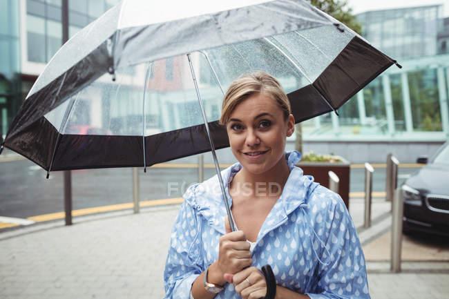 Portrait de femme attrayante tenant parapluie pendant la saison des pluies — Photo de stock
