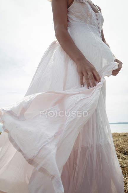 Mittelteil einer unbeschwerten Frau im weißen Kleid, die auf dem Feld steht — Stockfoto