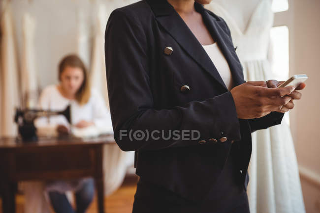 Seção intermediária do designer de moda usando telefone celular no estúdio — Fotografia de Stock