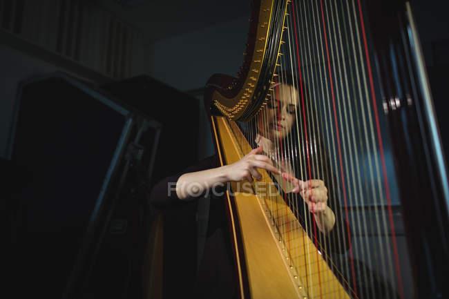 Aufmerksame Frau spielt Harfe in Musikschule — Stockfoto