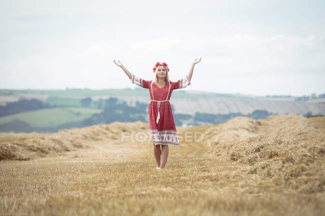 Carefree blonde woman standing in field with open arms — Stock Photo