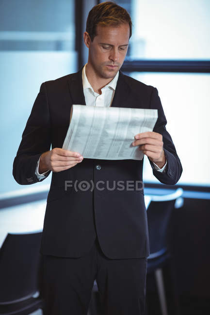 Businessman reading a financial report in office — Stock Photo