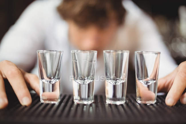 Bartender preparing and lining shot glasses for alcoholic drinks on bar counter at bar — Stock Photo