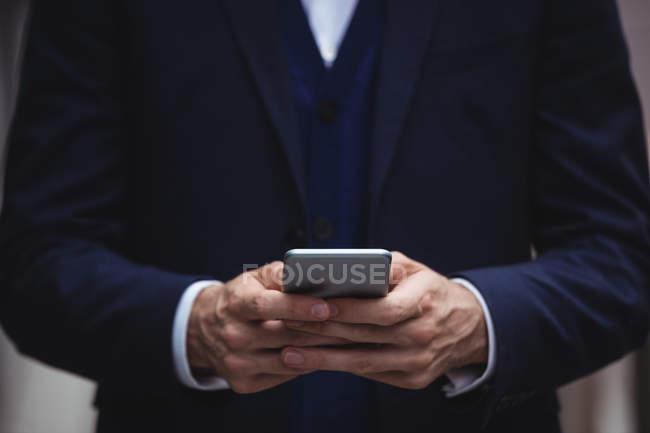 Розділ середині бізнесмен, за допомогою мобільного телефону — стокове фото