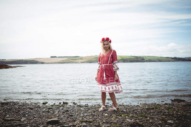 Attractive blonde woman in red dress and flower tiara standing near river and looking at camera — Stock Photo