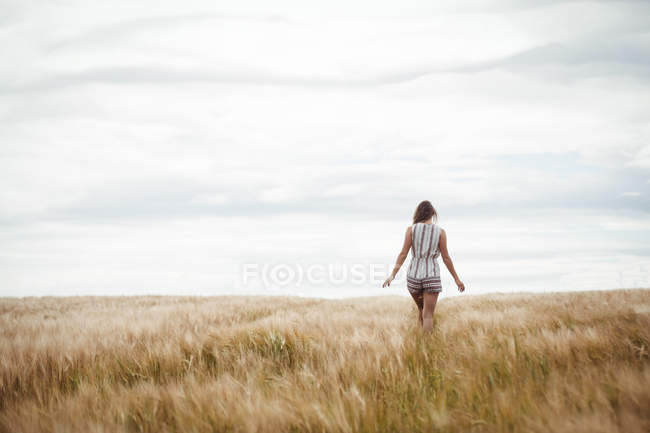 Rear view of woman walking through wheat field on sunny day — Stock Photo