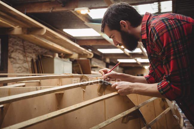 Man measuring a wooden plank in boatyard — Stock Photo