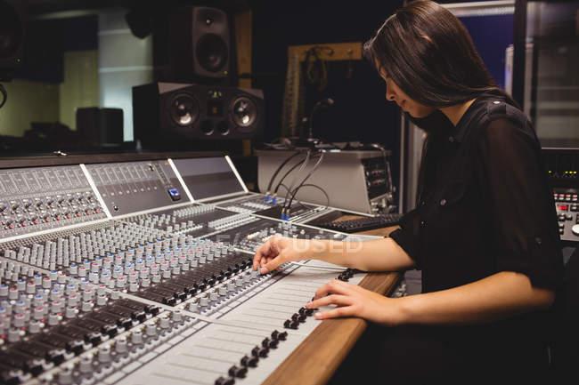 Female student using sound mixer in a studio — Stock Photo