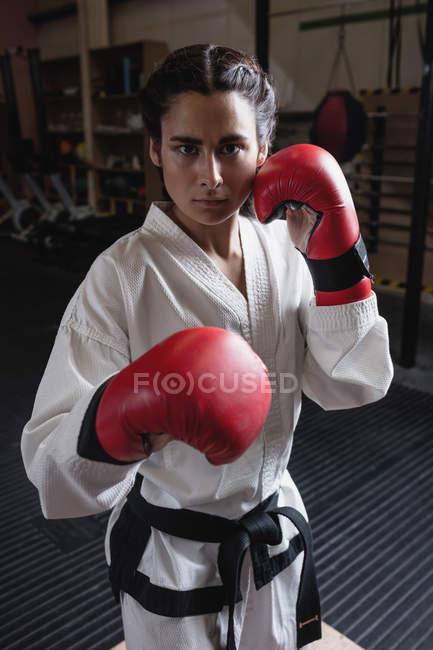 Porträt einer Boxerin in roten Boxhandschuhen, die im Fitnessstudio in die Kamera blickt — Stockfoto