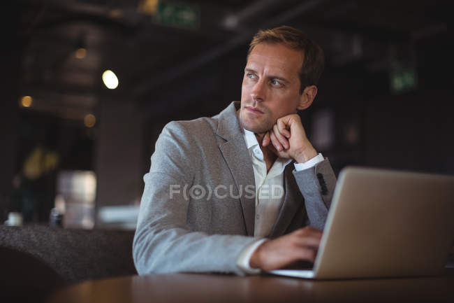 Thoughtful Business man using laptop at desk in office — Stock Photo